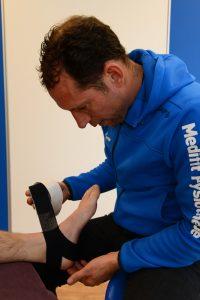 De fysiotherapeut helpt door medical taping toe te passen