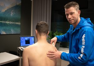 De fysiotherapeut gebruikt echotherapie om de schouden van de patiënt te onderzoeken.